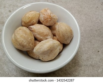 candlenut or kukui in white bowl over grey texture background