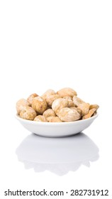 Candlenut seed in white bowl over white background