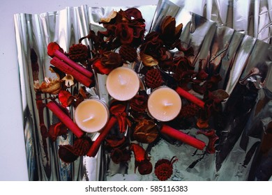 Candles and artificial roses on the foil.