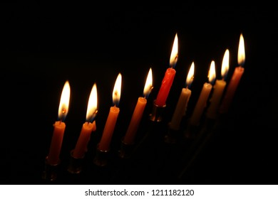 the candles burn brightly on the dark background