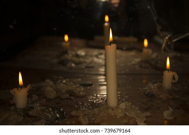 Candles burn in the dark dirty table. Preparing for the terrible ritual.