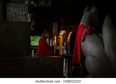 candles burning in ancient japanese shrine with kitsune fox statues, stone temple with lit candle, shinto shrine