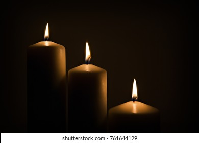 Candles burning burning brightly in the dark background