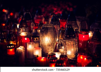 candles burning in lanterns at night during All Saints Day