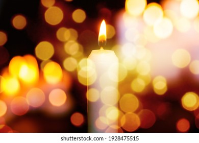 Candles burning light in a church background