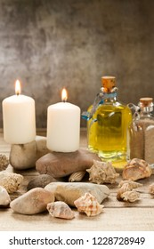Candles burning on stones with seashells  and essential oil on wood table and unfocused grey background