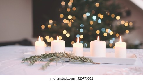 Candles Burning on the Table in front of Abstract Blurred Christmas Lights Bokeh Background. Served Dinner Table near Christmas Tree. Winter Holidays Concept.