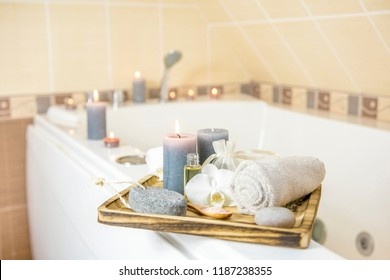 Candles burning and spa essentials on wooden tray in bathroom, essential oil, bath salt on wooden spoon, pumice stone, towel, sea stone, white orchids. Spa products set conception.