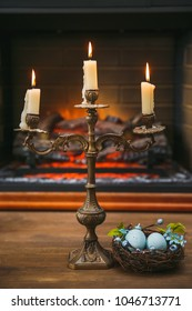 Candles in candelabras and Easter eggs in a nest on the background of a fireplace.