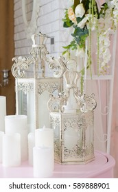 Candles with candlesticks on the pink table