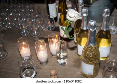 Candles and champagne with glitter set out for guests at a party.