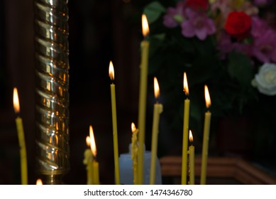 candles in the church burn on a dark background
