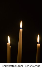 A lot of candles in dark room, five or six white and tall standing candles with flame
