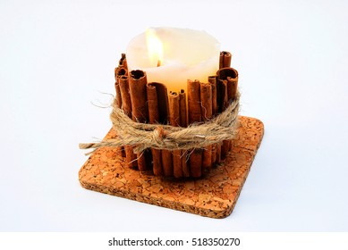 Candles decorated with cinnamon sticks on a white background.