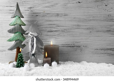 Candles with fir trees in a snow over wooden background, still life
