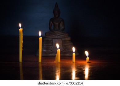 Candles Flame and Background Buddha statue.