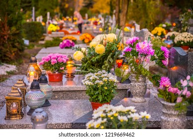 Candles and flowers on graves on All Saints Day in Poland