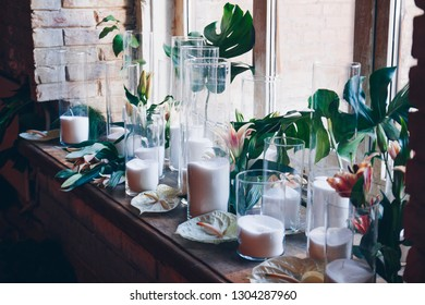 Candles in glass flasks on window sill with lily flowers and monstera leaves. Wedding decorations