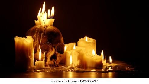 Kerzen und menschlicher Schädel im Dunkeln, Nahaufnahme