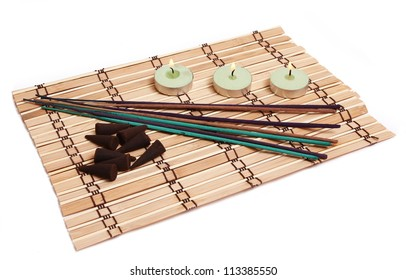 candles, incense cones and sticks on bamboo mat isolated on white