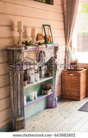 candles in the interior. home decor.  the country house decor is in the details.white - pink heather in autumn basket. decorative fireplace, decorated with paintings, flowers, books and candles