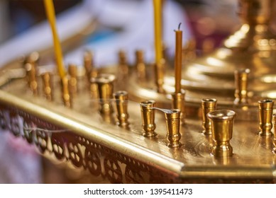 Candles in a large golden chandelier in the Orthodox Church, close-up