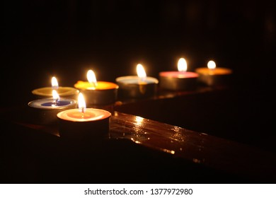 Candles lined on the fence in the dark night time. Sweet memories ceremony. Memorial of someone who passed away with love. Romantic scene with some space for your text.