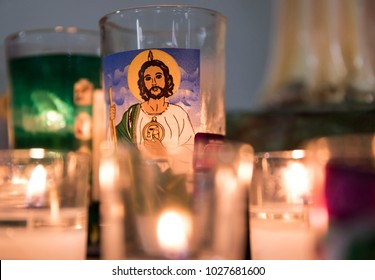 Candles lit in a temple with the image of Saint Jude Tadeo
