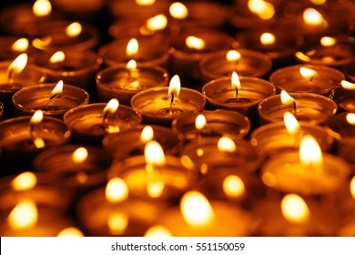 Candles. Many burning candles in dark. Yellow candles on black background.