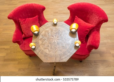 Candles on a antique side table with intarsia and red chair