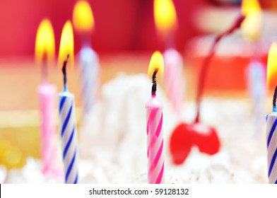 Candles on the birthday cake. Narrow depth of field. Close-up. Orange tint.
