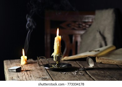 candles on the table with the book and pocket watch