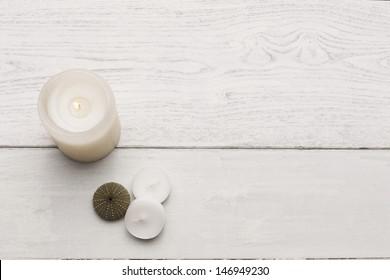 Candles on white hardwood. Studio shot.