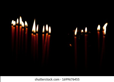 A lot of candles with placene on a dark black background