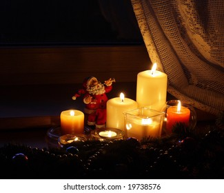 Candles  and Santa Claus with Christmas decorations in dark interior