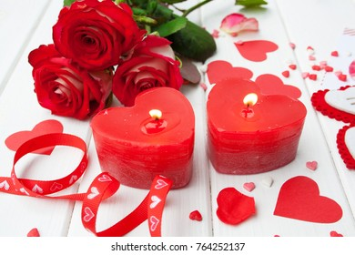 candles in the shape of heart and red roses valentines day on a white wooden background