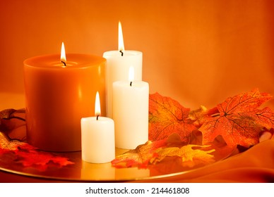 Candles and silk autumn leaves against gold background.