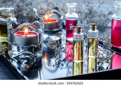 Candles. Small bottles of aromatic oil. Dry flowers. Natural cosmetics. Relax. Rest. Therapy massage. Selective focus. Dark glossy background