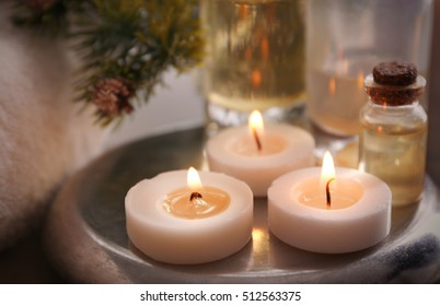 Candles with spa oil and Christmas decorations, closeup