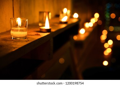 Candles in temple or candle in glass jar. Celebration light with complete black and blurred background. Selective focus