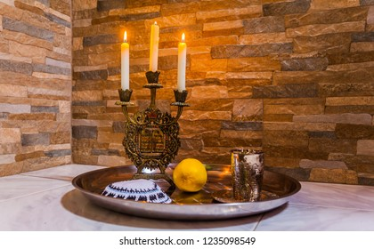 Candlestick with burning candle, silver glass for blessing and a white yarmulke. Still life with objects Judaica. Background stone wall. Concept of artistic photography