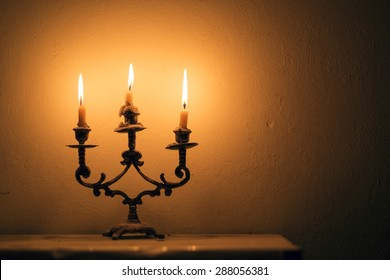 Candlestick with burning candles against a wall and fades into a shadow during a power outage