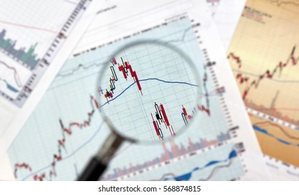 Candlestick graphs focus gap on forex chart under magnifying glass, business and financial concept.