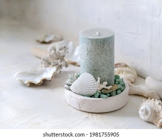 The candlestick with a light green candle, decorated with seashells, stones and corals.