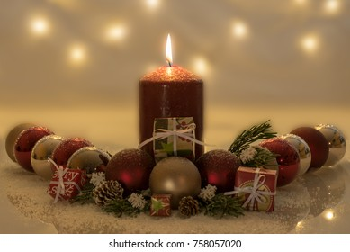 Candlight with christmas balls and fir in snow with wooden background