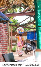 Candolim, Goa/ India - December 21, 2017: Indian woman carries goods on her head for sale on the market.