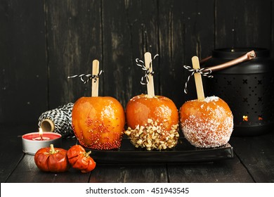 Candy apples. Traditional kids dessert for Halloween party. Dark style autumn card, selective focus