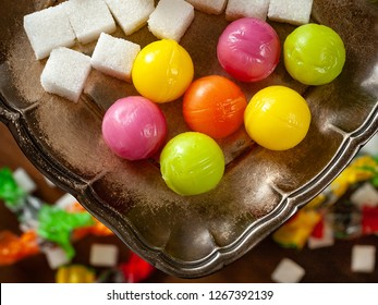 Candy balls and pieces of sugar. Colored dragees hard fruit candy and sugar stacked on a silver saucer, wooden background. The concept of sweet life.