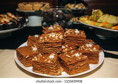 Candy bar for birthday or wedding celebration. Chocolate homemade cake with walnut in the top. Tasty sweet food on the table.
