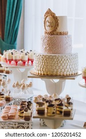 Candy bar with a lot of cookies and fruits during the wedding. chocolate fountain and wedding cake. Coktails and drink at the table